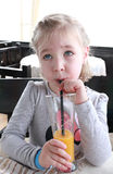 La petite fille douce boit du jus d'orange par une paille tout en se reposant à la table Photos stock