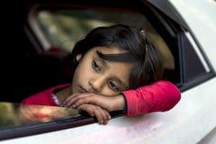 La petite fille douce a fatigué et se reposant sur le rebord de fenêtre de la voiture blanche mobile chez Himachal Pradesh images stock