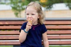 La petite fille drôle (3 ans) mangent la crème glacée  Image stock