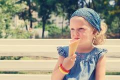 La petite fille drôle (3 ans) mangent la crème glacée  images stock