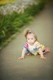 La petite fille drôle avec la trisomie 21 rampe le long du chemin Images stock