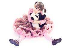 La petite fille embrasse le panda Image stock