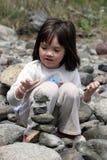 La petite fille empile des roches Photographie stock libre de droits
