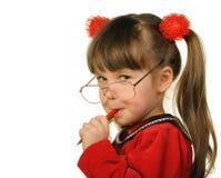 La petite fille en grandes glaces et avec le crayon lecteur image stock