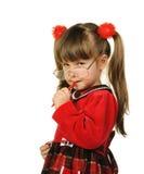 La petite fille en grandes glaces et avec le crayon lecteur Photo stock