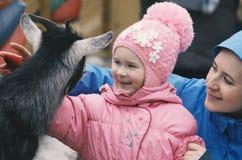 La petite fille en présence de la mère sourit heureux image libre de droits