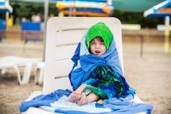 La petite fille enveloppée en serviettes pour chauffer, expression du visage photos libres de droits