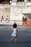 La petite fille essaye d'atteindre le vol de bulle de savon Photo stock