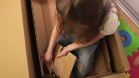 La petite fille essayent d'améliorer sa boîte en carton banque de vidéos