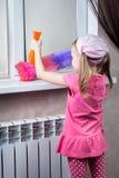 La petite fille essuie la poussière avec la brosse Image libre de droits