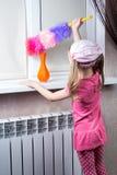 La petite fille essuie la poussière avec la brosse Photos stock