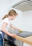 La petite fille essuie le cooktop Photographie stock
