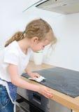 La petite fille essuie le cooktop Photos libres de droits
