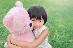 la petite fille est bonne amie avec l'ours et se reposer de nounours au p Photographie stock