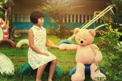la petite fille est bonne amie avec l'ours et se reposer de nounours au p Images libres de droits