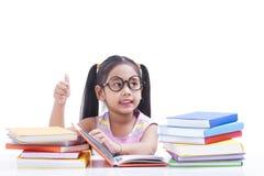 La petite fille est livre de lecture Photos stock