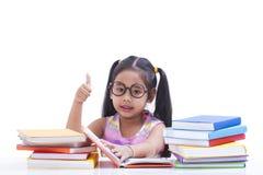 La petite fille est livre de lecture Photo stock