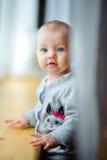 La petite fille est par la fenêtre Image libre de droits