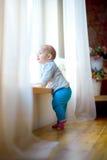 La petite fille est par la fenêtre Images libres de droits