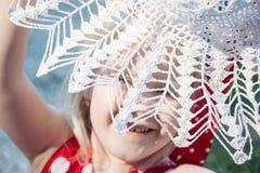 La petite fille est riante et se cachante derrière le chapeau de crochet Images libres de droits
