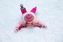 La petite fille est tombée au patinage de glace Photo libre de droits