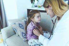 La petite fille est tombée malade Un docteur est venu chez elle et a écouté elle avec un stéthoscope Photo libre de droits