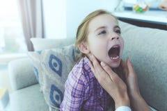 La petite fille est tombée malade Un docteur est venu chez elle et a examiné sa gorge Image stock