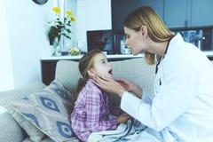 La petite fille est tombée malade Un docteur est venu chez elle et a examiné sa gorge Photographie stock