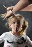 La petite fille est très étonnée en peignant des cheveux avec les mains femelles photo stock
