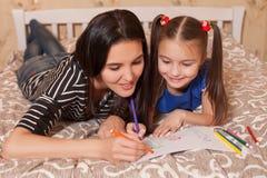 La petite fille et la mère dessinent le mensonge sur un lit Image libre de droits