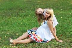 La petite fille et la mère enceinte posent sur l'herbe verte en somme Image libre de droits