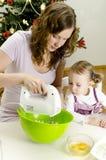 La petite fille et la mère préparent des biscuits Images libres de droits