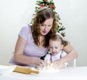 La petite fille et la mère préparent des biscuits Photo libre de droits