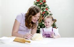 La petite fille et la mère préparent des biscuits Images stock