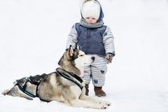 La petite fille et le chien jouent dans la neige Photographie stock