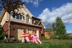 La petite fille et le garçon avec des biscuits s'assied sur l'herbe Photographie stock