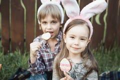 La petite fille et le garçon mangent un biscuit de pain d'épice sous forme d'oeuf de pâques Image libre de droits