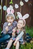 La petite fille et le garçon mangent un biscuit de pain d'épice sous forme d'oeuf de pâques Photo stock