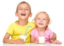 La petite fille et le garçon mignons sont lait boisson Photos stock