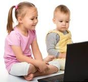 La petite fille et le garçon regardent l'ordinateur portatif Photo libre de droits