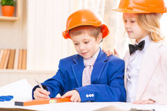 La petite fille et le garçon travaillent avec des papiers de construction Photo stock