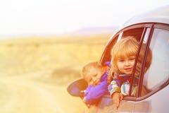 La petite fille et le garçon voyagent en voiture en montagnes Image stock