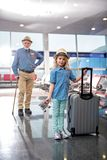 La petite-fille et le grand-père optimistes se tiennent ensemble au salon d'aéroport Image libre de droits