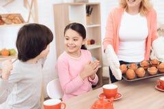La petite-fille et le petit-fils heureux sont amusement parce que la grand-mère a fait des petits gâteaux cuire au four Photographie stock libre de droits