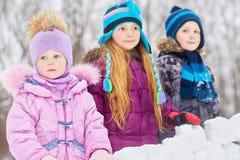 La petite fille et les enfants plus âgés se tiennent derrière le mur des blocs de neige Photographie stock libre de droits
