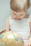 La petite fille examinant un globe Photo libre de droits