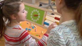 La petite fille faisant des maths s'exerce avec sa mère à la maison banque de vidéos