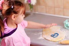 La petite fille fait cuire des biscuits Photographie stock libre de droits