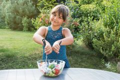La petite fille fait cuire la salade dans le jardin Photographie stock