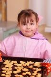 La petite fille fait des biscuits cuire au four Photos stock